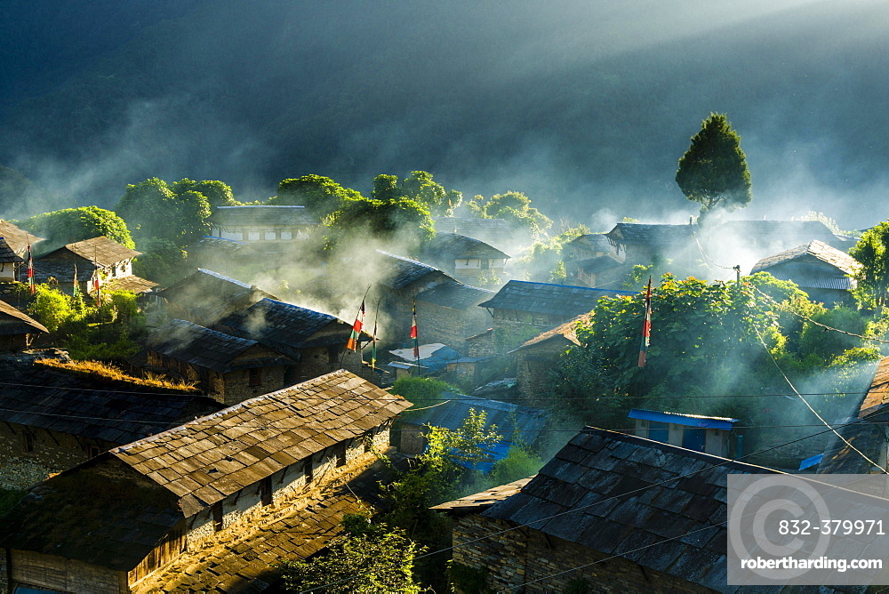 View on village in morning light, smoke is coming out of the houses, Ghandruk, Kaski District, Nepal, Asia