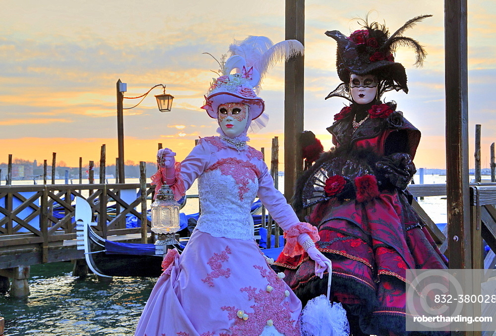 Disguised couple with Venetian masks on the lagoon, carnival in Venice, Italy, Europe