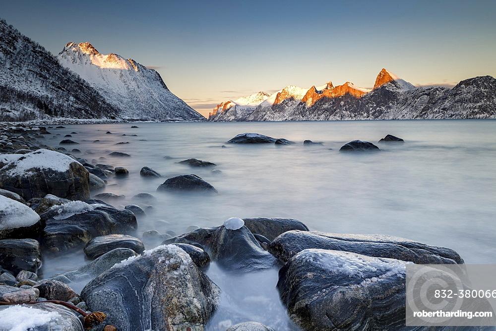 Norwegian fjord, snow-covered mountains at sunset, near Mefjordvær, Senja Island, Norway, Europe
