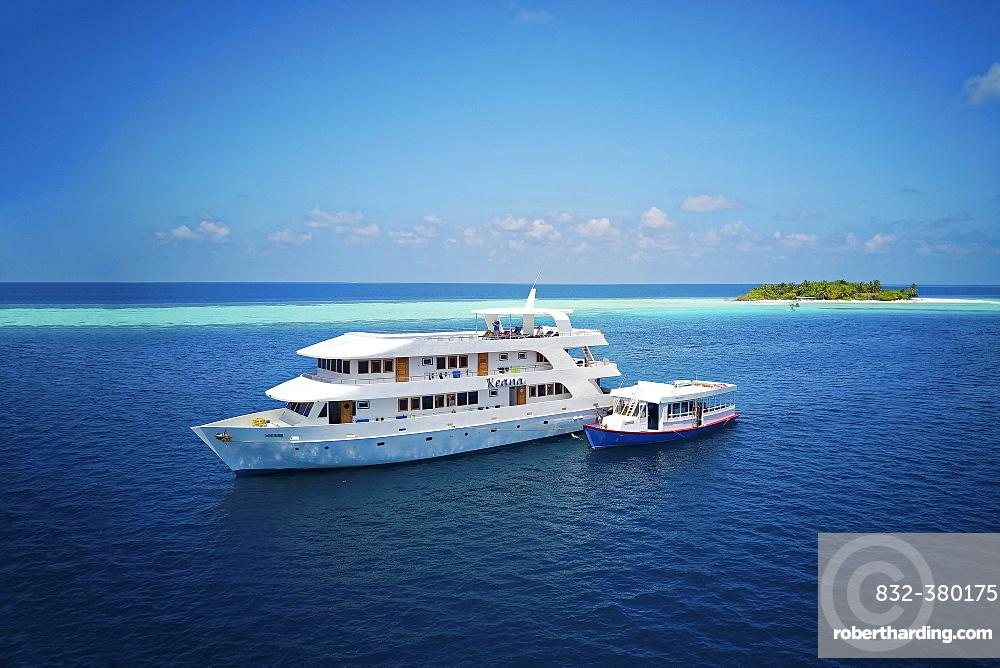Diving safari ship MS Keana with diving dhoni anchored off an uninhabited palm island, Ari Atoll, Indian Ocean, Maldives, Asia