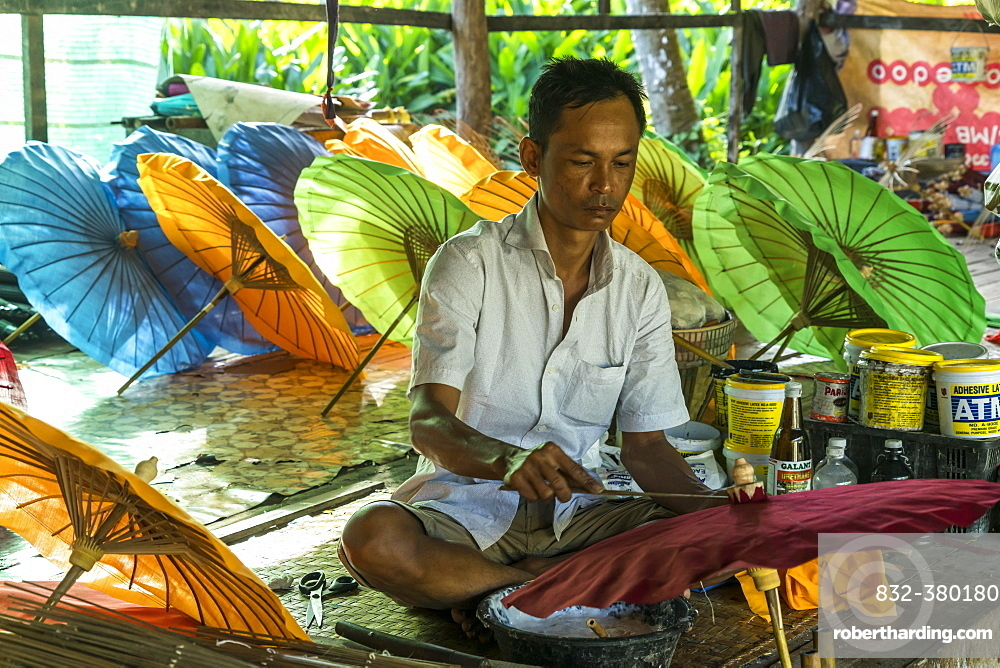 Local man working on multi-colored umbrellas, Pathein, Myanmar, Asia
