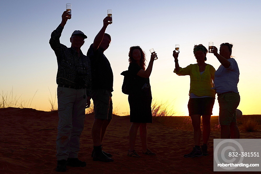Tourists at the sundowner with glass in hand, backlight at sunset, Kglagadi Transfrontier Park, Northern Cape, South Africa, Africa