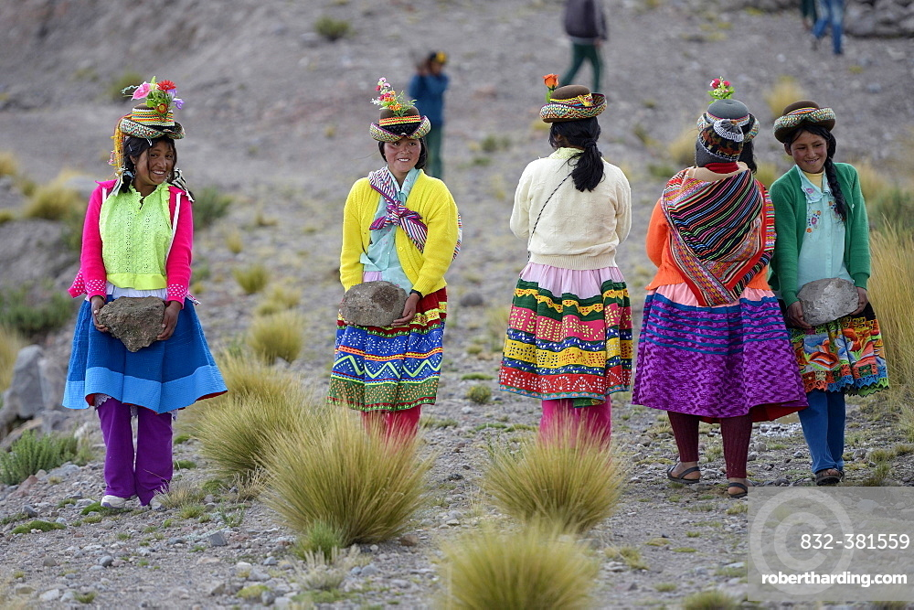 Young women carrying heavy stones to secure the shores of an artificial lake for irrigation, Quispillacta, Ayacucho, Peru, South America