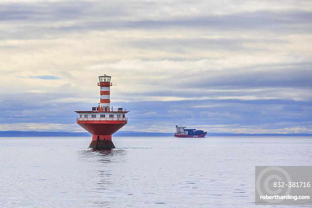 Lighthouse Phare du Haut-Fond Prince in Saint Lawrence River with freighter in the back, Tadoussac, Québec Province, Canada, North America