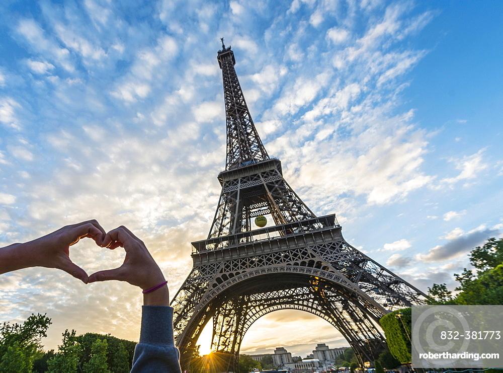 Hands forming heart, sunset behind Eiffel Tower, Paris, Ile-de-France, France, Europe