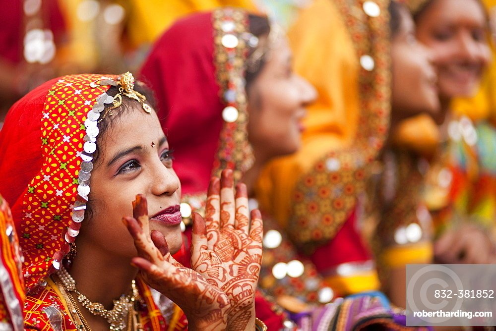 Young women in typical colourful traditional Rajasthani costume and henna painted hands at the camel market and livestock market, Pushkar Mela, Pushkar, Rajasthan, India, Asia