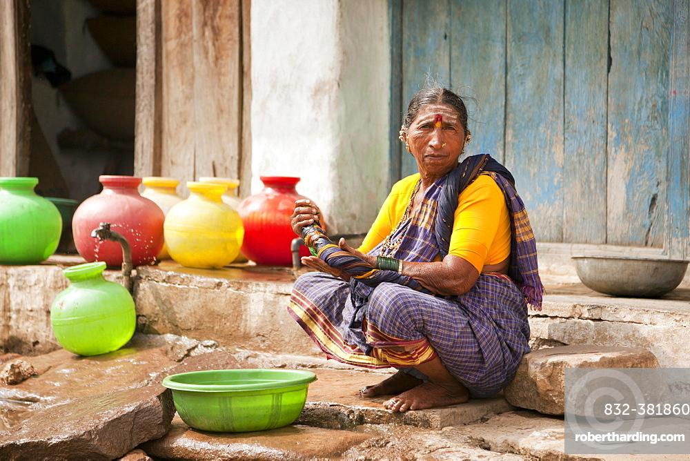 Elderly woman washing her hands, Aihole, Karnataka, India, Asia