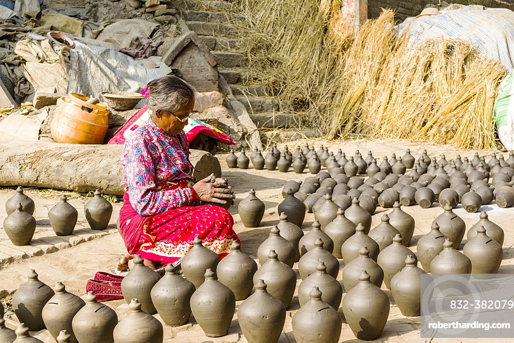 A woman is working at pottery in the streets, Bhaktapur, Kathmandu, Nepal, Asia
