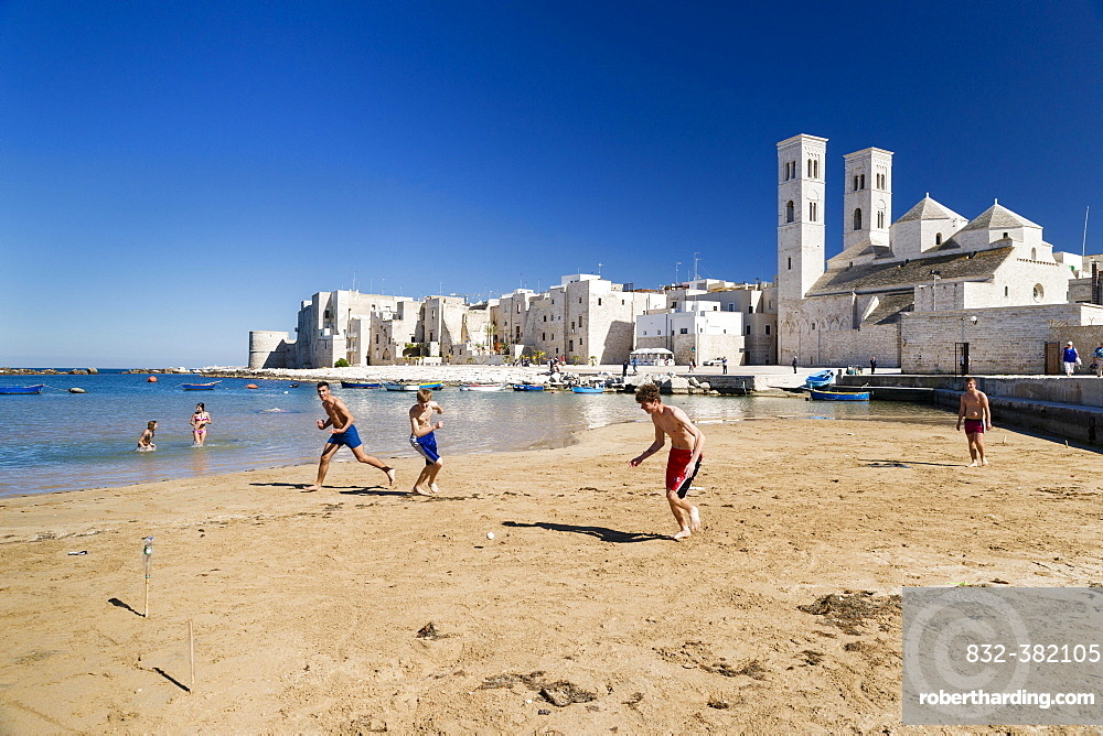 Teenagers playing football onthe beach, harbor, historic centre, Romanesque Old Cathedral, San Corrado and Torrione Passari, Molfetta, Bari Province, Apulia, Italy, Europe