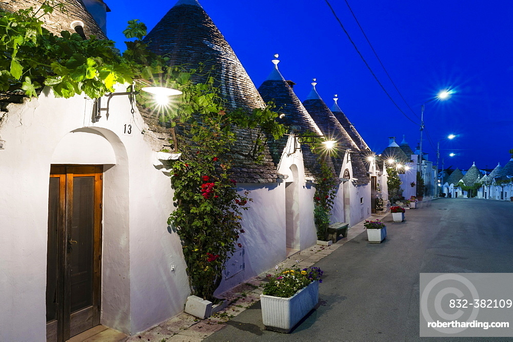 Trulli, traditional round houses, trullo settlement, at dusk, blue hour, Rione Monti district of Alberobello, Valle d'Itria, Trulli Valley, Apulia, Italy, Europe