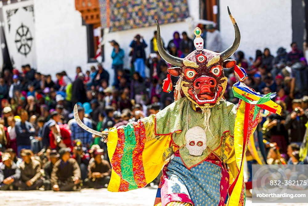 Monks with big wooden masks and colorful costumes are performing ritual dances at Hemis Festival in the courtyard of the monastery, Hemis, Jammu and Kashmir, India, Asia