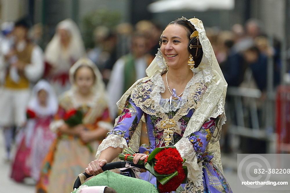Fallas festival, young woman in a traditional costume during the parade in the Plaza de la Virgen de los Desamparados, Valencia, Spain, Europe