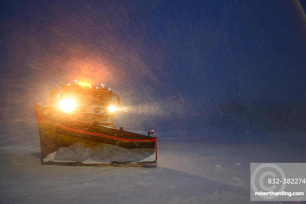 Snowplow in the arctic blizzard during the polar night, Longyearbyen, Svalbard, Norway, Europe