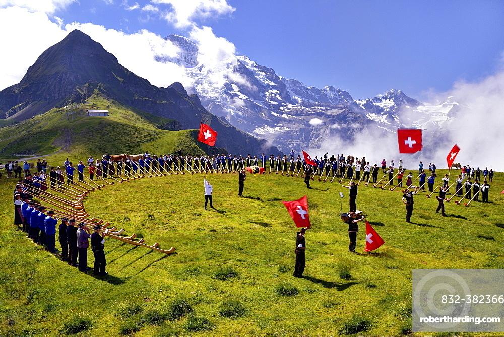 Alphorn blowers and flag throwers, Grosses Alphorntreffen festival, on Mannlichen mountain, Kleine Scheidegg pass, Canton of Bern, Switzerland, Europe