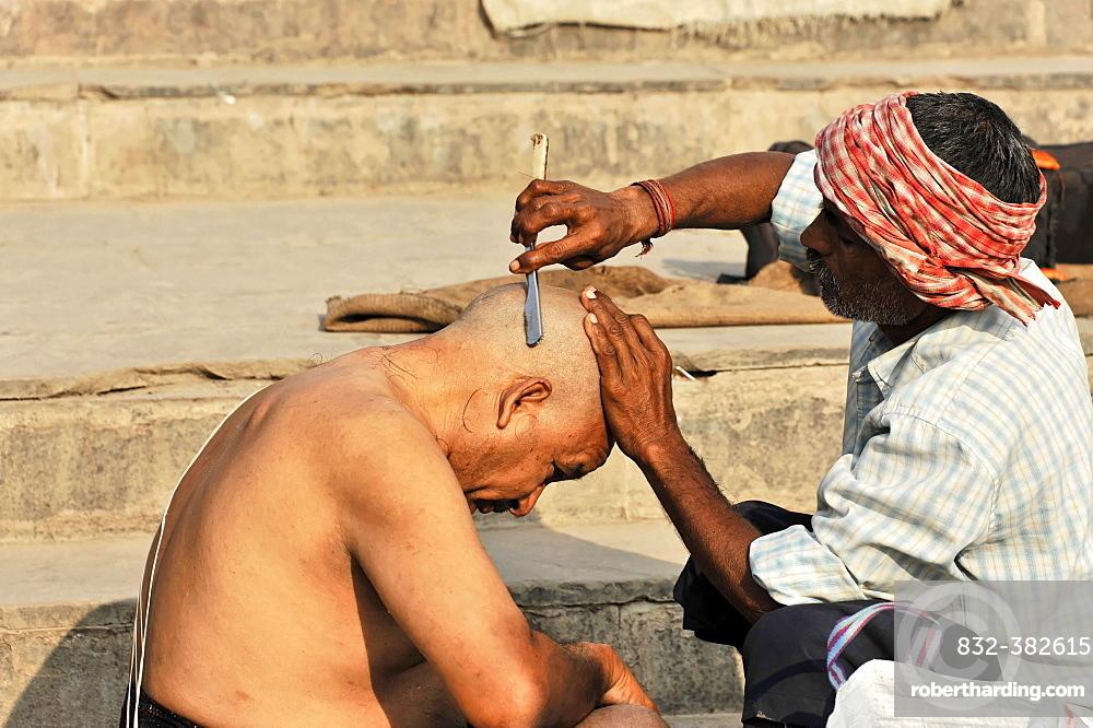 Ritual hair cutting on the Ganges, Varanasi, Benares, Uttar Pradesh, India, Asia