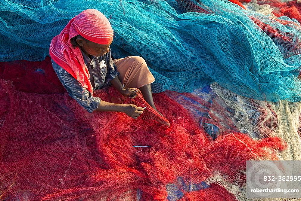 Fisherman repairing fishing nets, Varkala, Kerala, India, Asia