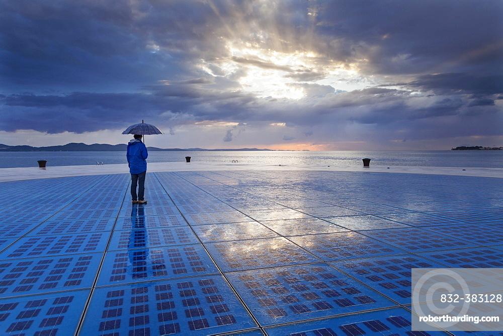 "Woman holding an umbrella, standing on the solar art installation """"Greeting to the Sun"""", Zadar, Dalmatia, Croatia, Europe"