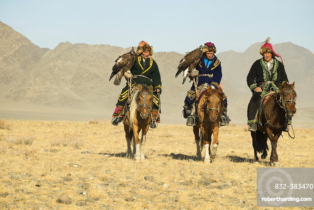Three Kazakh eagle hunters on their horses on the way to the Eagle Festival in Sagsai, Bayan-Oelgii Aimag, Mongolia, Asia