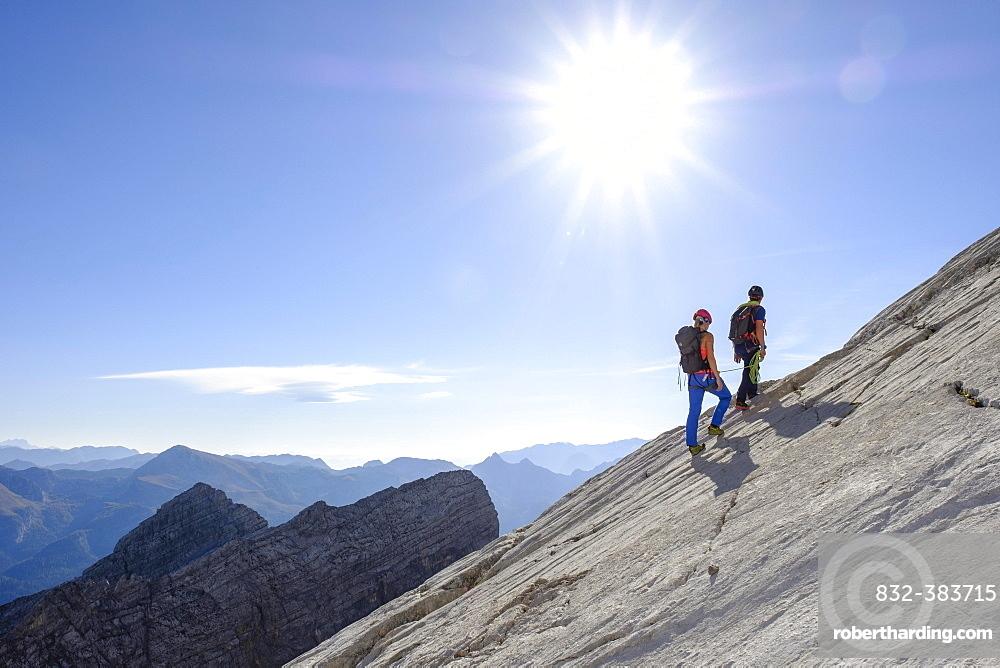 Mountain guide guiding a young woman on a short rope through a rock face, Wiederroute, Watzmann, Schonau am Konigsee, Berchtesgadener Land, Bavaria, Germany, Europe