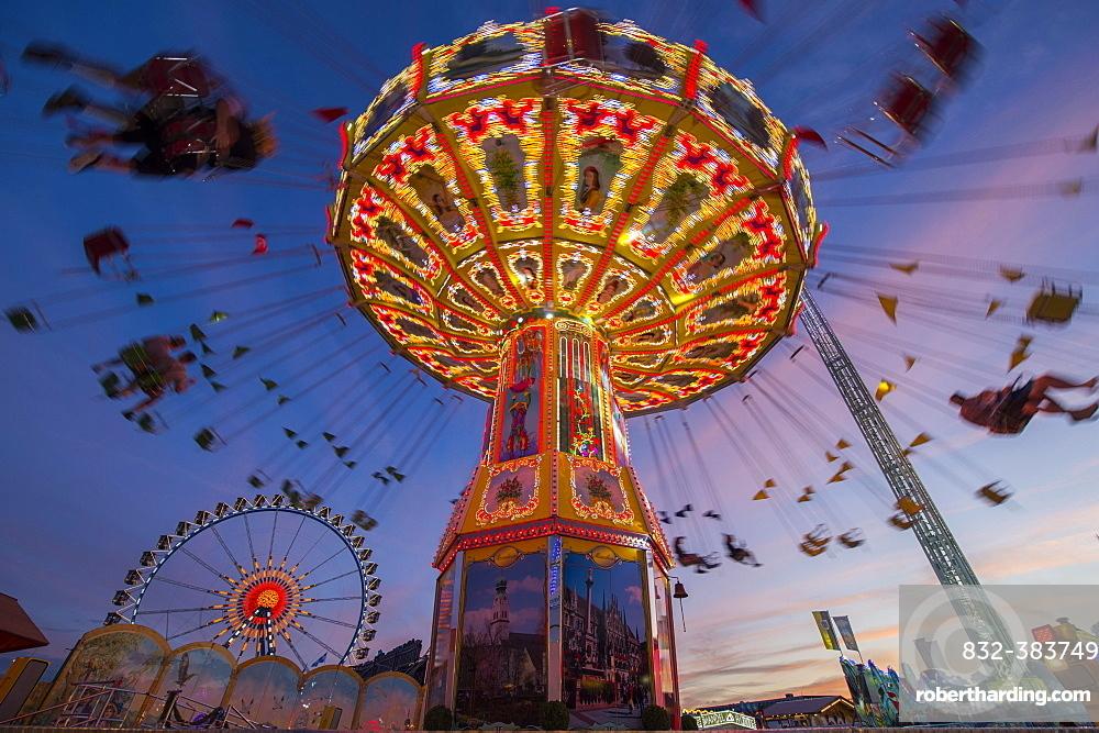 Rotating chain carousel and ferris wheel at the blue hour, Oktoberfest, Munich, Bavaria, Germany, Europe