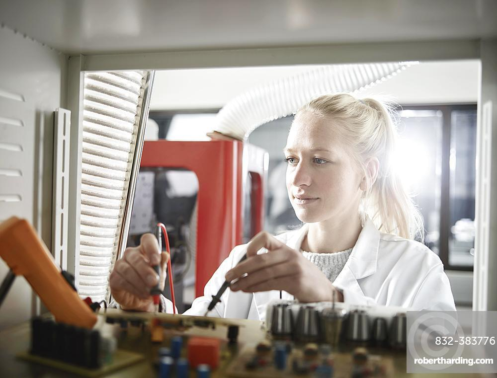 Young woman with white lab coat measuring controller with meter, Austria, Europe