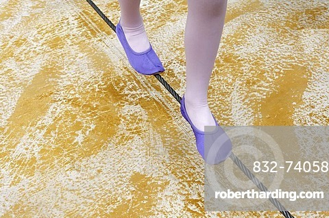 Little girl in ballet shoes balancing on a steel cable just above the ground