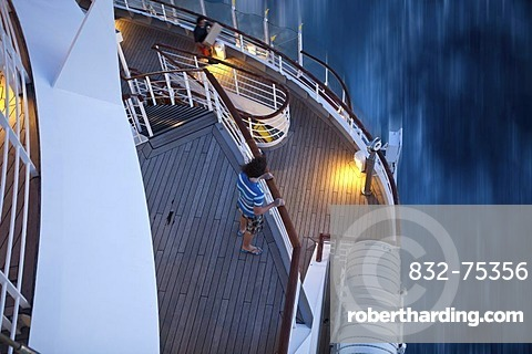 Young man standing at the railing at dusk, Aida Club Cruiser, during travel, Corsica, France, Europe - Attention: Restricted right of use! Please ALWAYS contact the press office before publishing this picture: AIDA Cruises, Am Strande 3d, 18055 Rostock, G