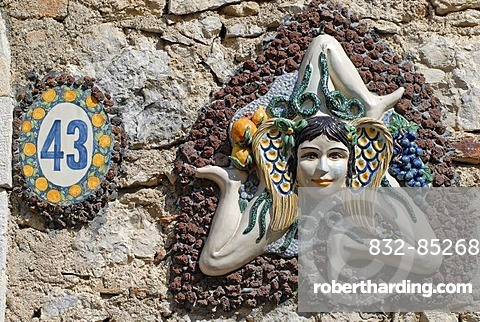 The symbol of Sicily, a girl's head surrounded by snakes and small wings with three running angled legs, sun wheel, on a wall, Taormina, Messina, Sicily, Italy, Europe