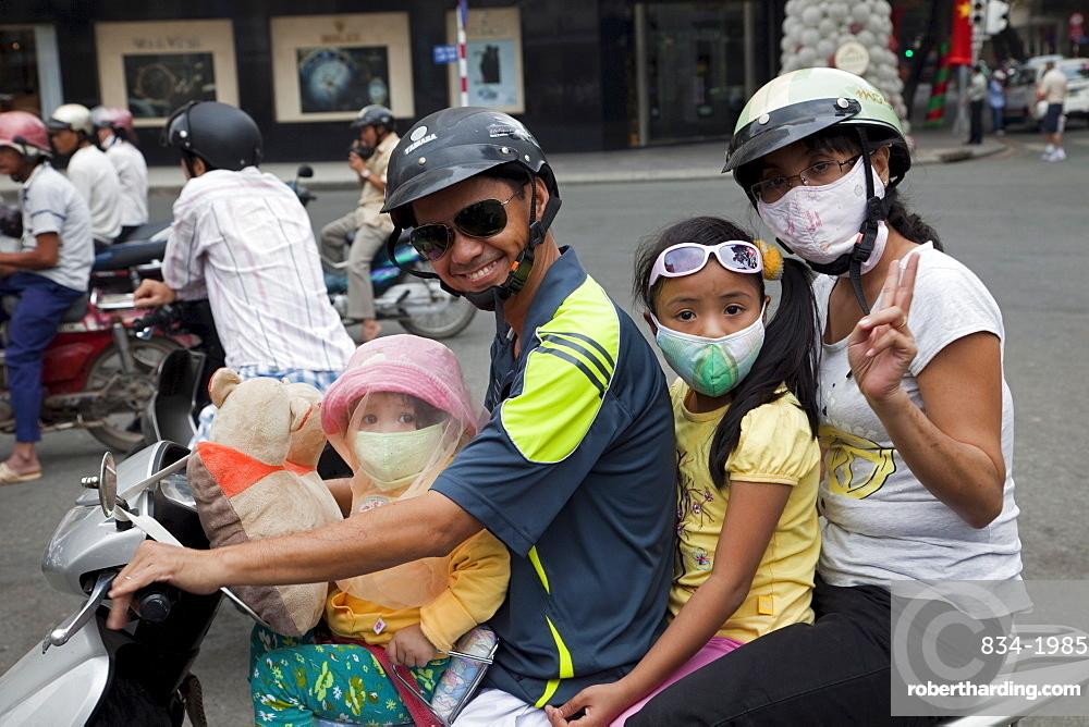 Motorbike passengers wearing pollution mask, Ho Chi Minh City, Vietnam, Indochina, Southeast Asia, Asia