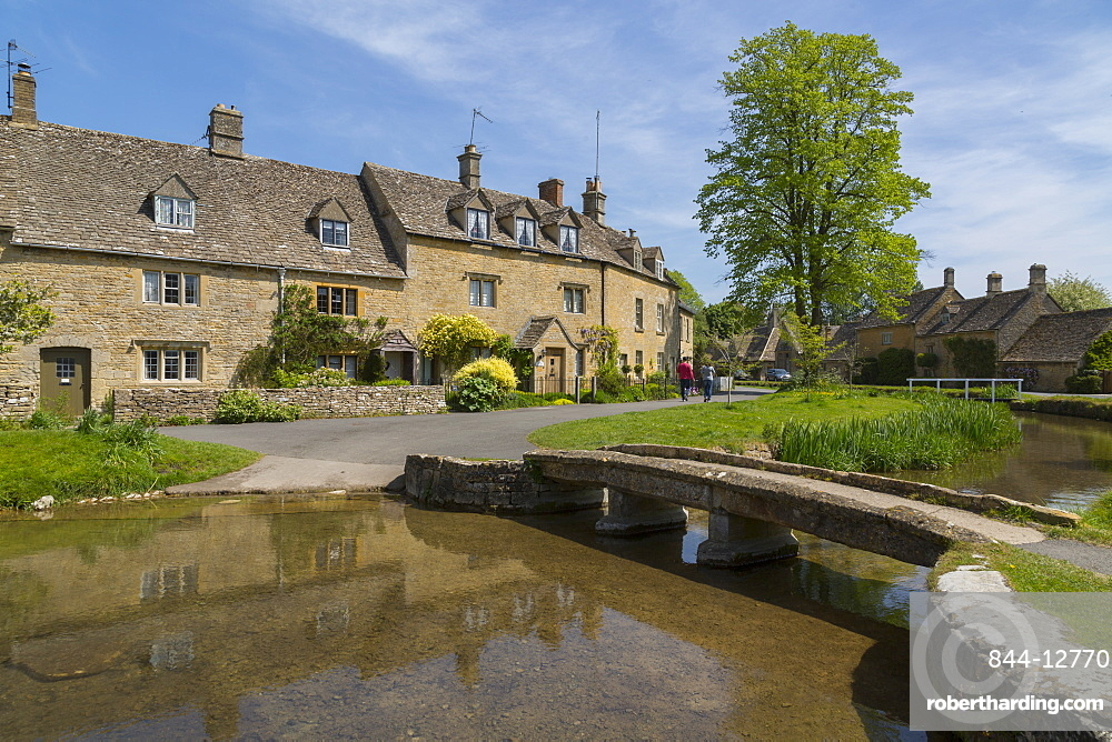 Cottages and footbridge over the River Eye in Lower Slaughter, Cotswolds, Gloucestershire, England, United Kingdom, Europe