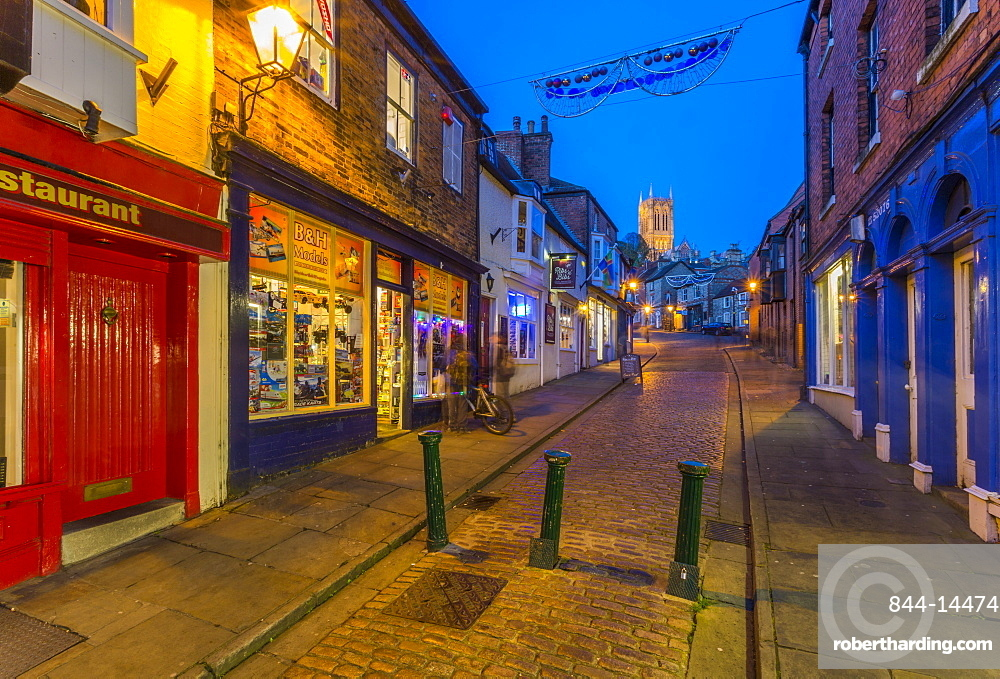 View of illuminated Lincoln Cathedral viewed from the cobbled Steep Hill at dusk, Lincoln, Lincolnshire, England, United Kingdom, Europe
