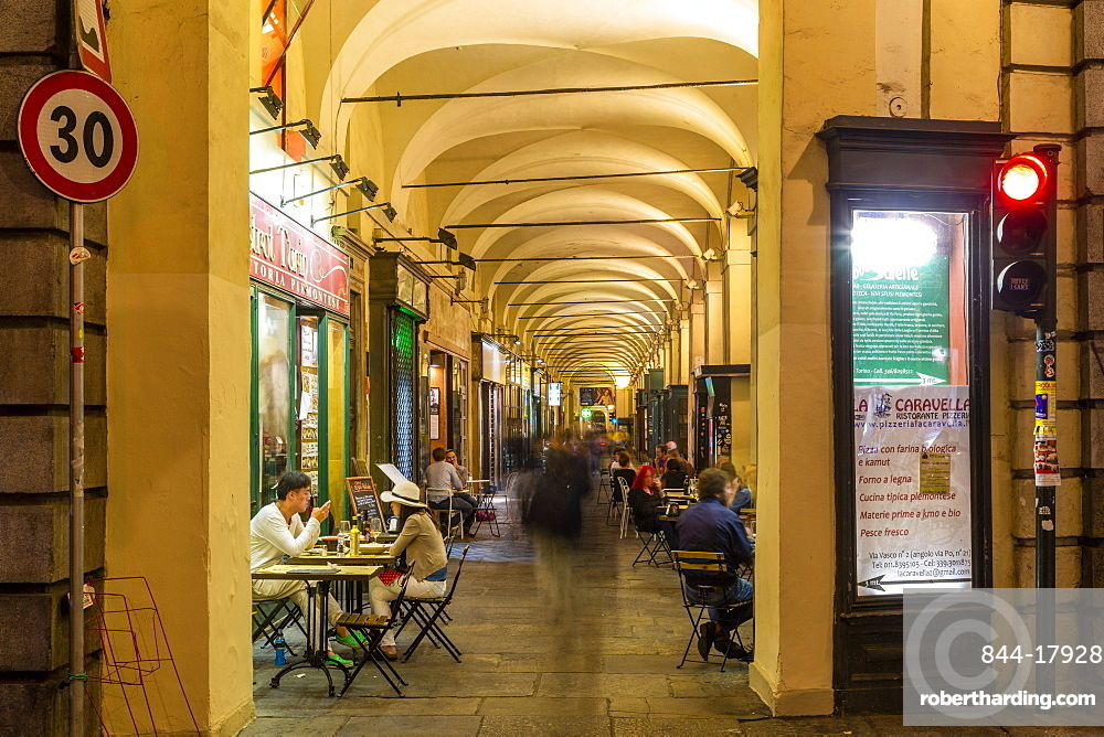View of Cafe under the arches in shopping arcade at dusk, Turin, Piedmont, Italy, Europe