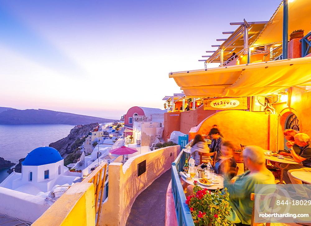 View of restaurant in Oia village overlooking the sea at dusk, Santorini, Cyclades, Aegean Islands, Greek Islands, Greece, Europe