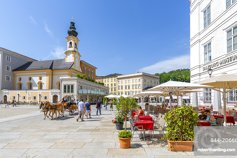View of St. Michaelskirche and restaurants in Residenzplatz, Salzburg, Austria, Europe