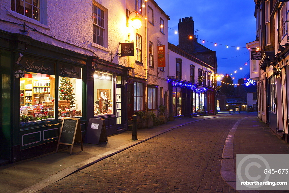 Independent shops and Christmas lights on Kirkgate, Ripon, North Yorkshire, Yorkshire, England, United Kingdom, Europe