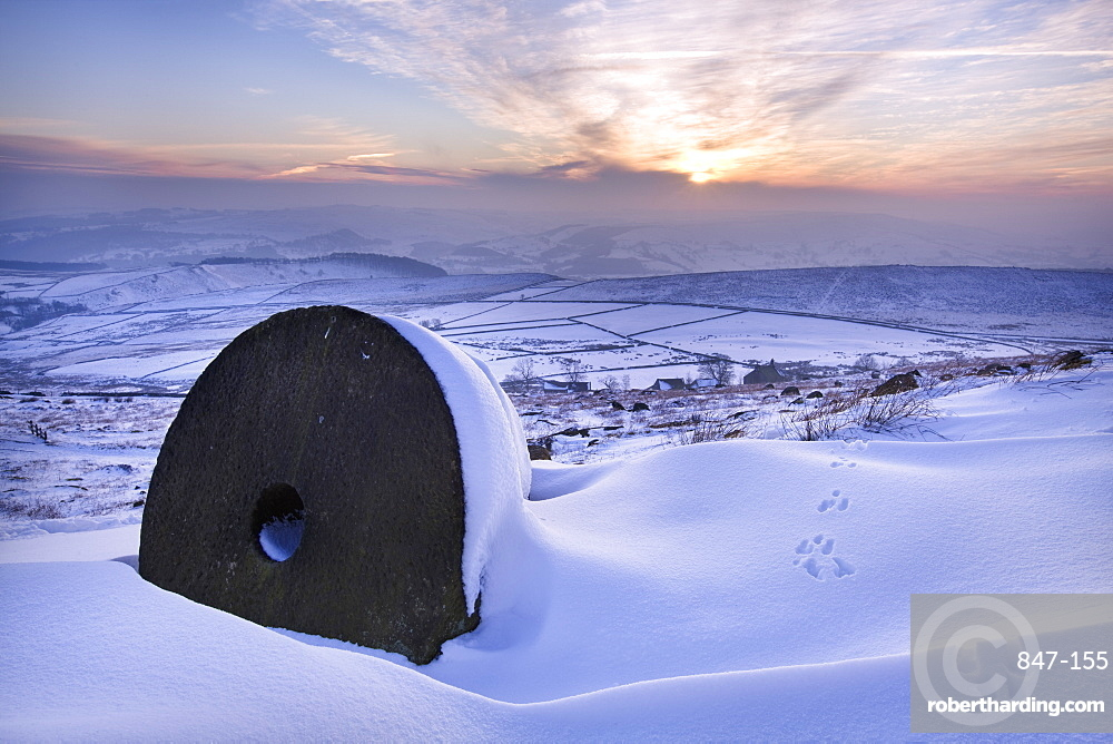 The last rays of sun on the snow and millstones of Stanage Edge, Derbyshire, England, United Kingdom, Europe