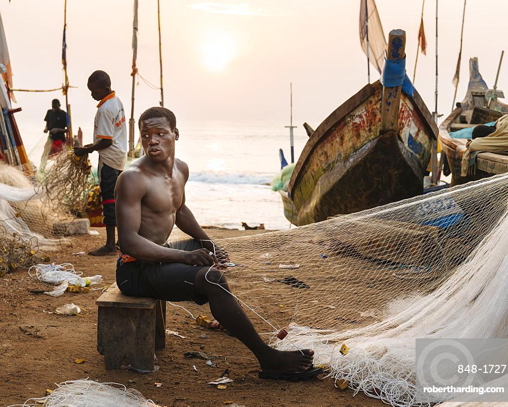 Fisherman fixing nets on beach in Cape Coast, Ghana