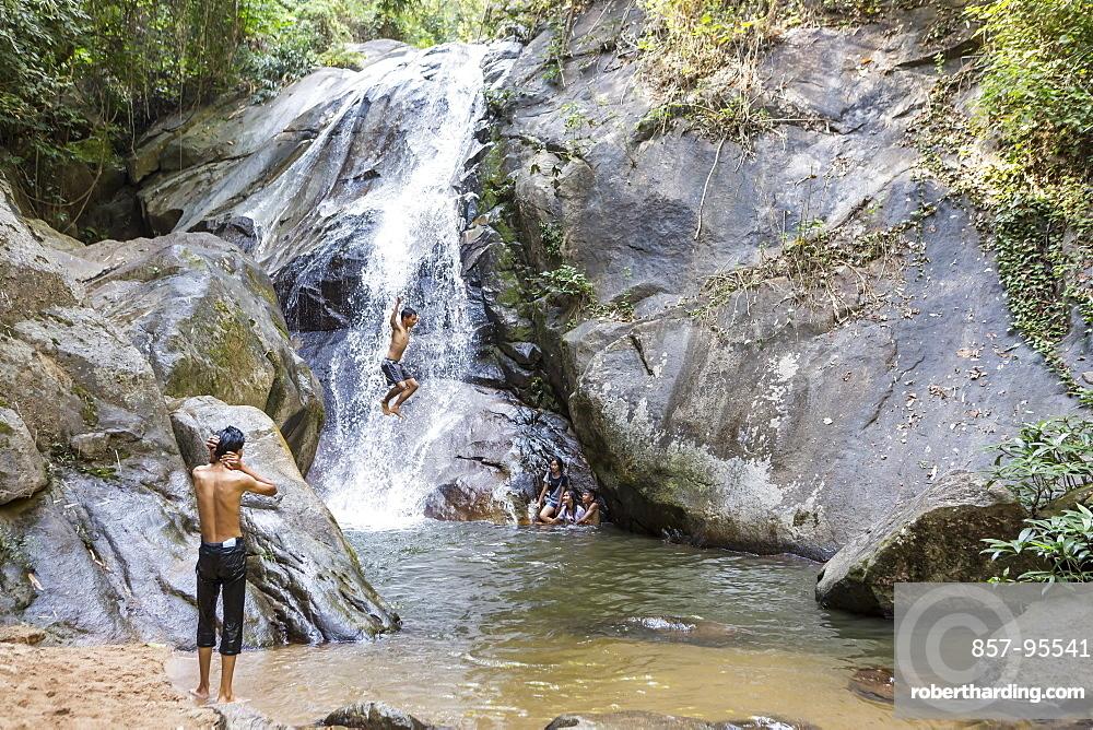 Shirtless boy jumping off rock at waterfall, Chiang Rai, Thailand