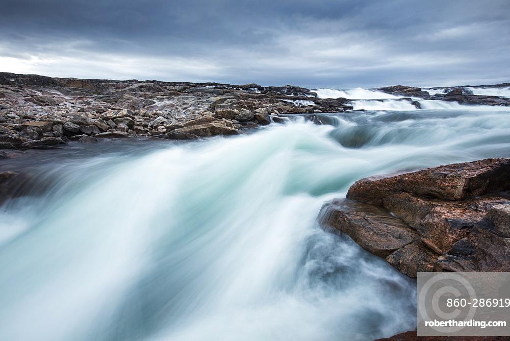 Blurred image of rushing waterfall near Bury Cove along west coast of Hudson Bay (Barren Coastline) 100 miles south of the Arctic Circle, Nunavut Territory, Canada