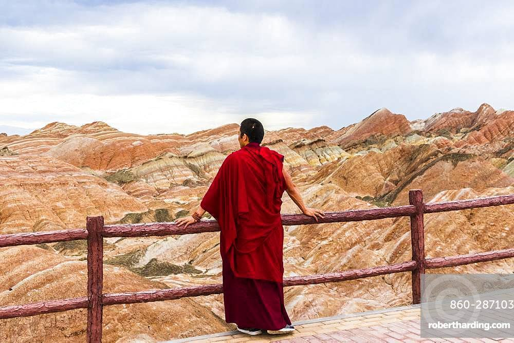 Monk and Eroded hills of sedimentary conglomerate and sandstone, Unesco World Heritage, Zhangye, China