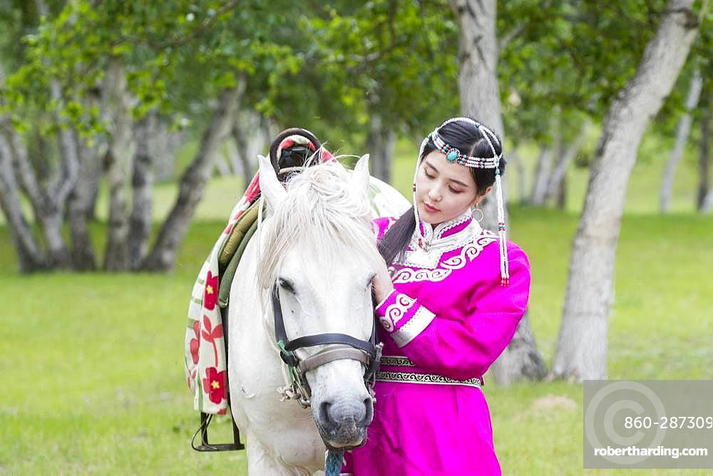 Mongol woman traditionnaly dressed with a horse, Mode, Bashang Grassland, Zhangjiakou, Hebei Province, Inner Mongolia, China
