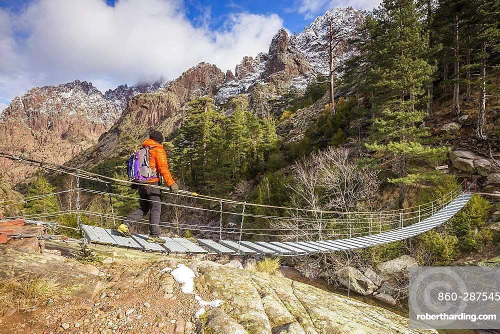 Hiker on the suspended footbridge of Spasimata on the GR 20, Cirque de Bonifatu, Corsica Regional Nature Park, Balagne, Corse-du-Sud, France
