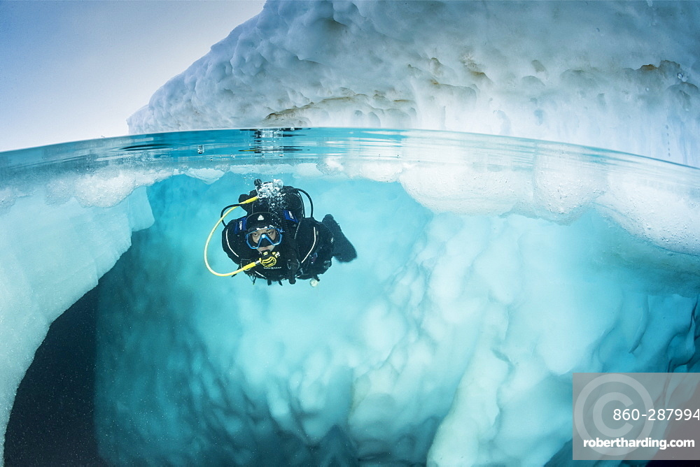 Spit image of a scuba diver diving close to an iceberg, only in springtime, when the hard winter slowly subsides, are the ice-cold waters suitable for divers who can dive around a iceberg that floats in crystal-clear water, Tasiilaq, East Greenland