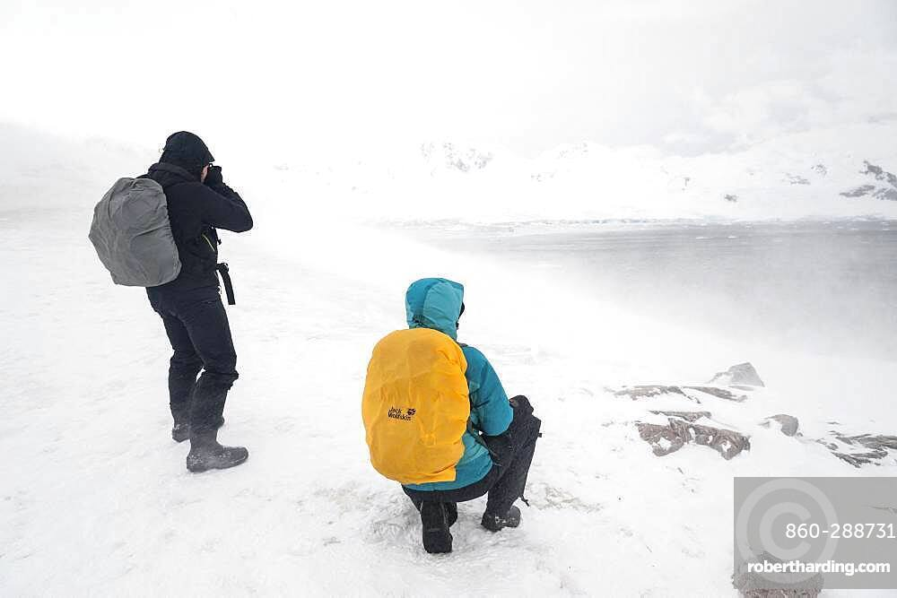 A snowstorm hits two tourists watching the landscape in Neko Harbour, Antarctica.