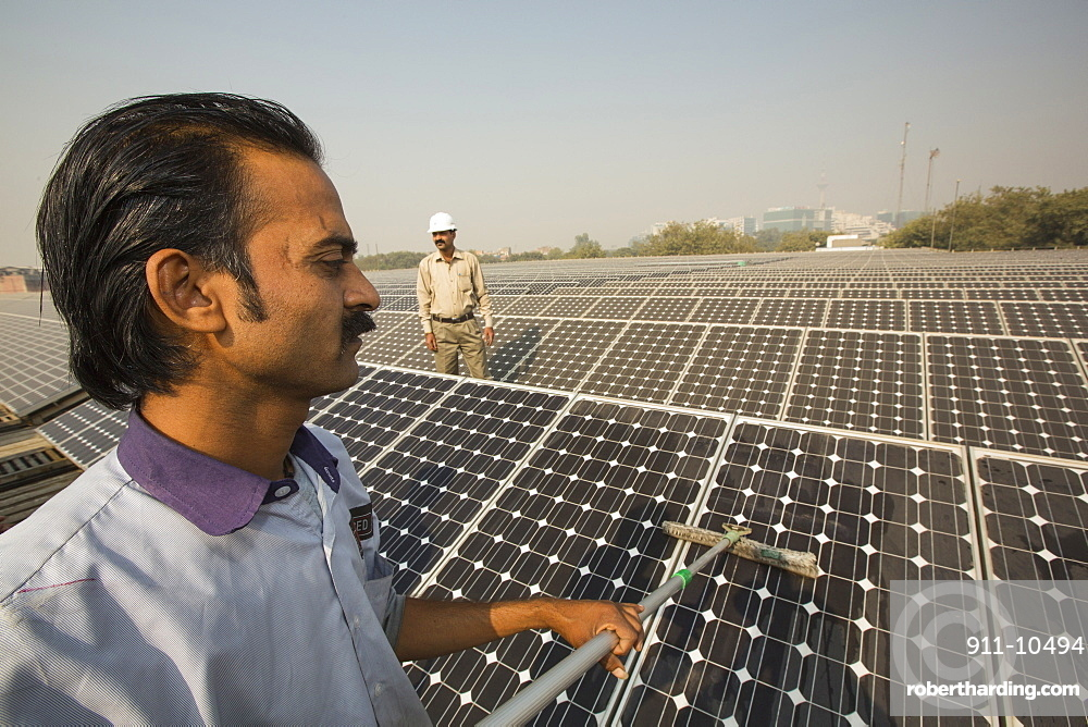 Workers washing the dust off solar panels at a 1 MW solar power station run by Tata power on the roof of an electricity company in Delhi, India, to make them more efficient.