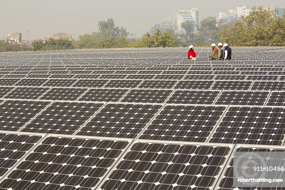 Workers at a 1 MW solar power station run by Tata power on the roof of an electricity company in Delhi, India.