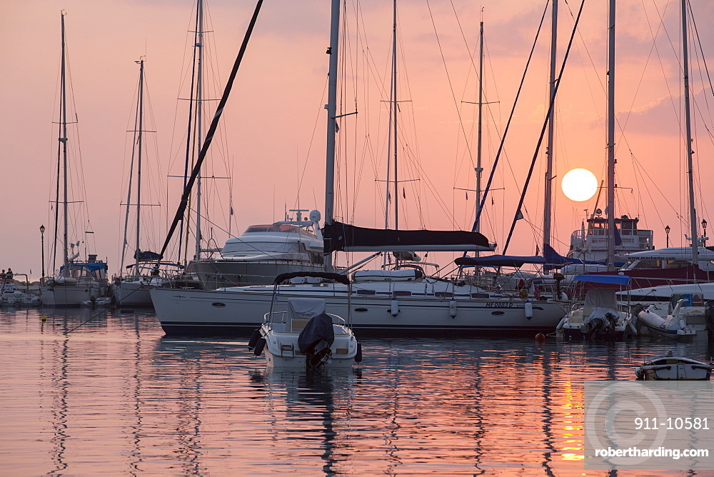 Sailing boats in the harbour at Sivota in Greece at sunset.