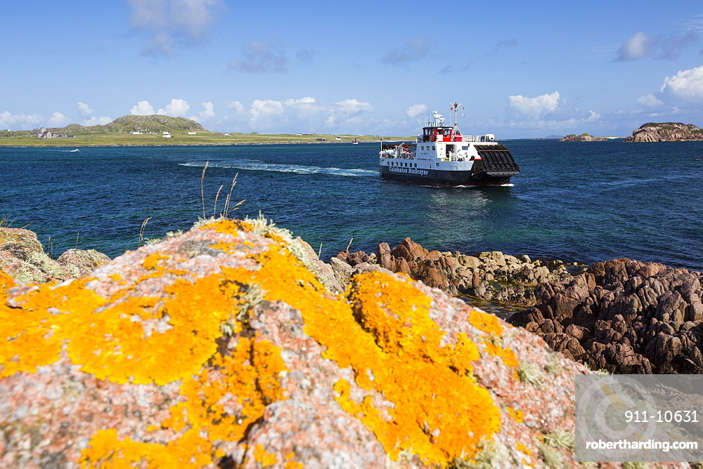Lichen covered granite boulders at Fionnphort Isle of Mull, Scotland, UK, looking towards Iona, with the Iona ferry.