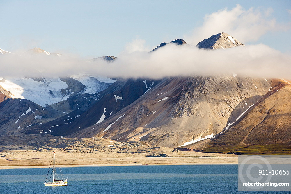 A mountain peak, peeping through the cloud at Bourbonhamna 77¬8 33'Äôn 15¬8 00'Äôe Spitsbergen; Svalbard, with a yacht sailing past.