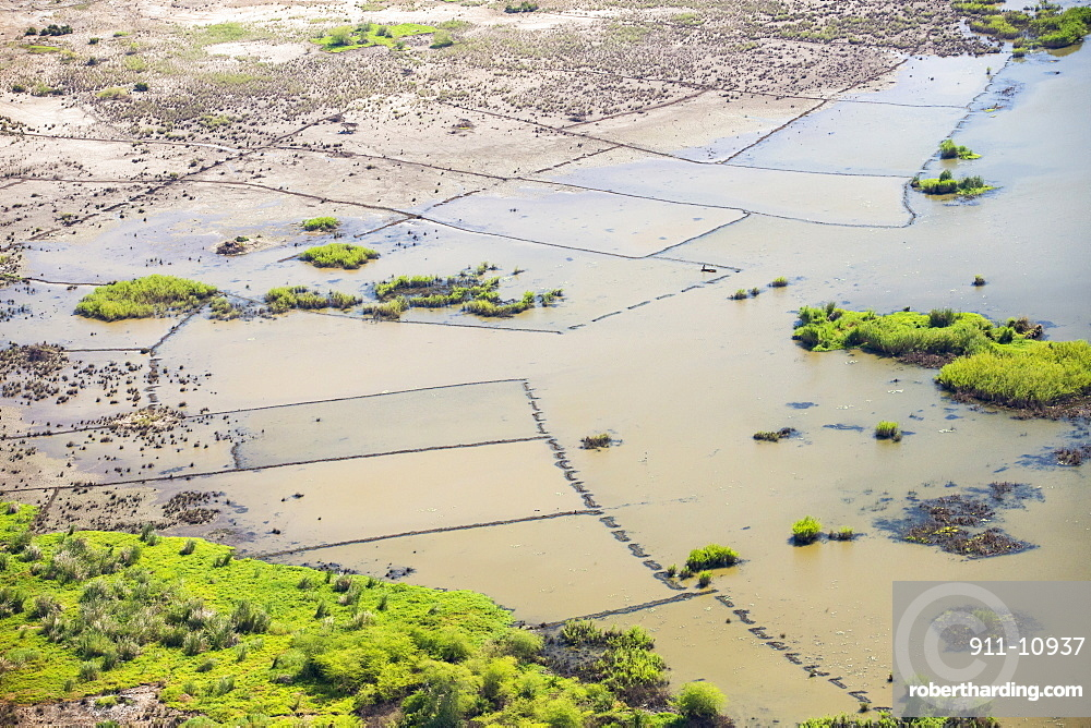 In mid January 2015, a three day period of excessive rain brought unprecedented floods to the small poor African country of Malawi. It displaced nearly quarter of a million people, devastated 64,000 hectares of land, and killed several hundred people. This shot taken from the air on a flight to Makhanga, which two months on, is still cut off by the floods when all rail and road connections were washed away, is looking down on the flood waters still sat on the flood plain, and the devastated farmland.